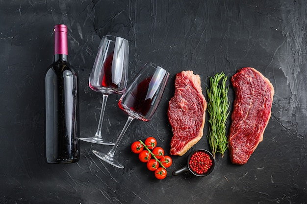 Rauwe picanha steaks met smaakmakers en kruiden in de buurt van fles en glas rode wijn, over zwart getextureerd tafelblad.