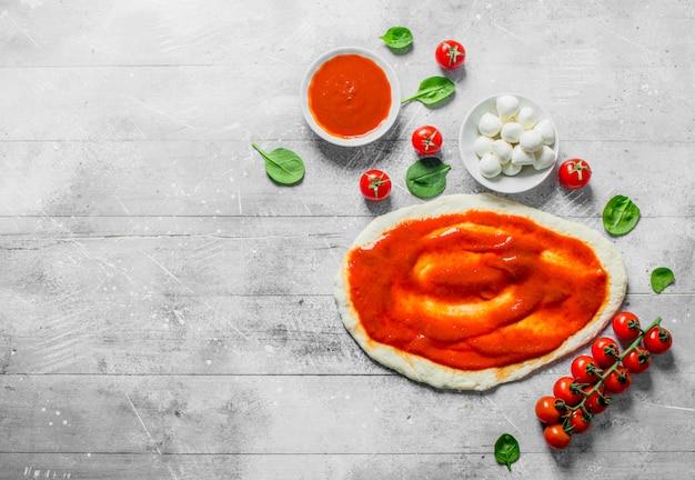 Rauwe pizza. deeg met mozzarella, tomatenpuree en spinazie. op witte houten achtergrond