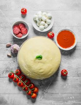 Rauwe pizza. deeg met worstjes, tomatenpuree, knoflook en mozzarella. op witte houten achtergrond