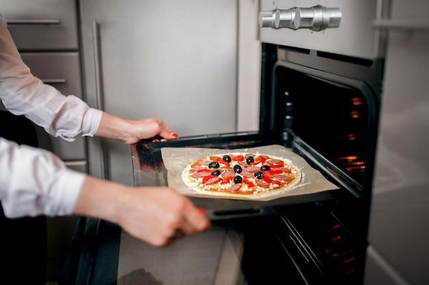 Rauwe pizza met ingrediënten op bakplaat