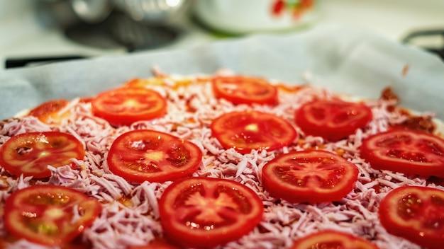 Rauwe pizza met vlees, kaas en tomaten