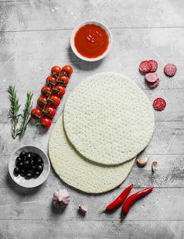 Rauwe pizza. rond deeg met olijven, worstjes en tomaten op witte houten lijst uitgerold