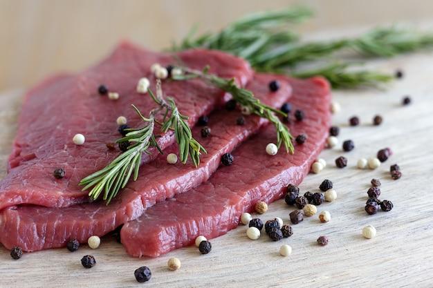 Rauwe plakjes mager rundvlees met peper en rozemarijn, close-up.