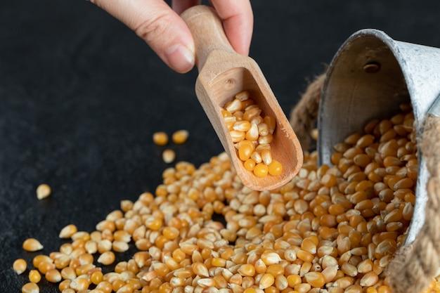 Rauwe popcorn met houten lepel op een donkere