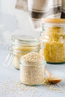 Rauwe quinoa korrels in pot. gezond vegetarisch eten op grijze keukentafel