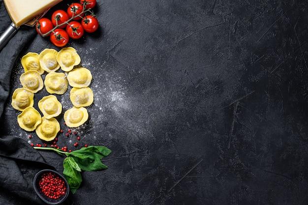 Rauwe ravioli. het proces van het maken van zelfgemaakte italiaanse ravioli. zwarte achtergrond. bovenaanzicht. ruimte voor tekst