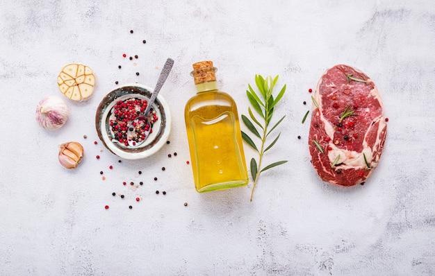 Rauwe rib eye steak opgezet op witte betonnen achtergrond. plat leggen van verse rauwe biefstuk met rozemarijn en kruiden op witte armoedige betonnen achtergrond bovenaanzicht.