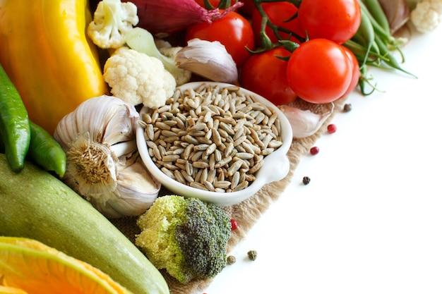 Rauwe rogge graan in een kom en groenten geïsoleerd op wit close-up