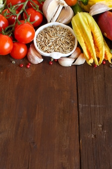Rauwe rogge graan in een kom en groenten op houten tafel met kopie ruimte