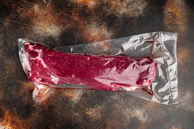 Rauwe runderfilet steaks mignon geheel gesneden in plastic luchtdichte verpakking, op oude donkere rustieke achtergrond, bovenaanzicht plat gelegd