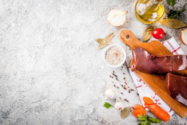 Rauwe runderlever met specerijen, kruiden en groenten, grijze stenen tafelblad weergave
