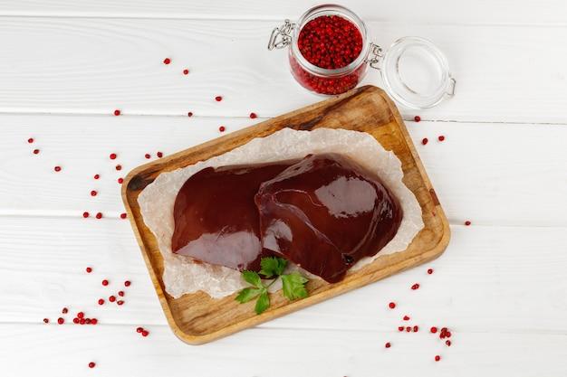 Rauwe runderlever op een houten bord op tafel