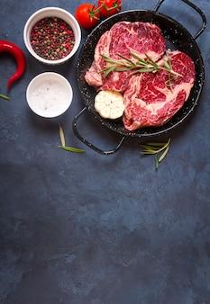 Rauwe sappige steaks met kruiden in een pan klaar om te roosteren op rustieke betonnen achtergrond.