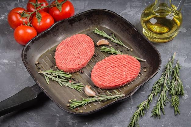 Rauwe schnitzel pan met rozemarijn en knoflook. grijze marmeren achtergrond.