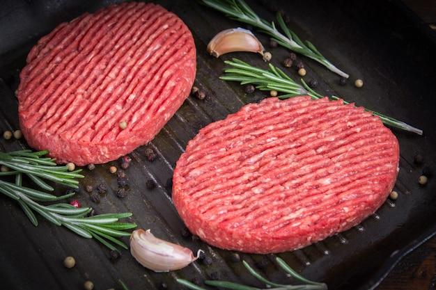 Rauwe schnitzel pan met rozemarijn en knoflook. houten bruine achtergrond.
