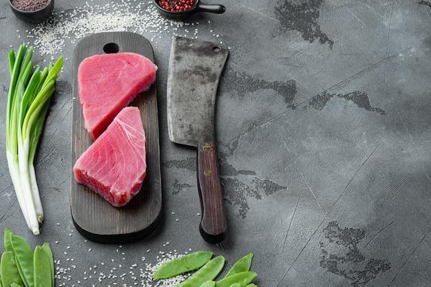 Rauwe sesam tonijnsteak ingrediënten set, op houten snijplank, en oud slagersmes, op grijze stenen tafel