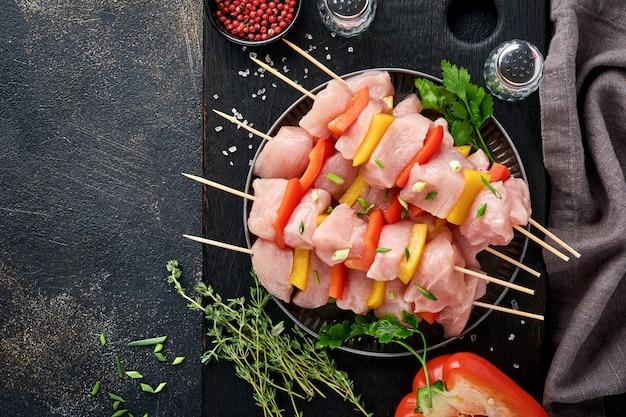 Rauwe shish kebab op een houten bord, specerijen, kruiden en groenten