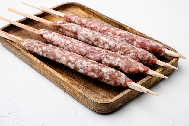Rauwe shish kebab spiesjes set, op witte stenen tafel achtergrond