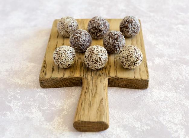 Rauwe snoep energie ballen close-up op het houten bord op de grijze betonnen achtergrond