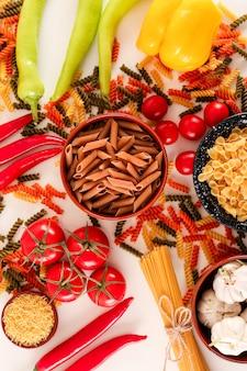 Rauwe spaghetti met tomaat groene chili peper en rode chili peper op een witte ondergrond