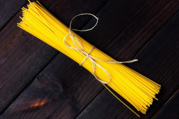 Rauwe spaghetti op een donkere achtergrond bovenaanzicht pasta op een houten donkere tafel