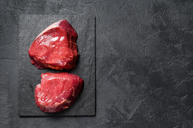 Rauwe steaks filet mignon bereid om te koken. ossenhaas. zwarte achtergrond. bovenaanzicht. ruimte voor tekst