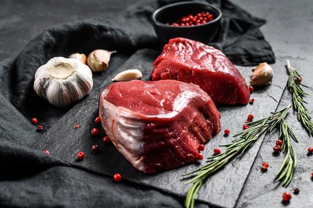 Rauwe steaksfilet mignon bereid om te koken ossenhaas. zwarte muur. bovenaanzicht