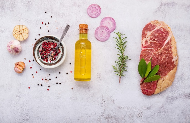 Rauwe striplion steak opgezet op witte betonnen achtergrond. plat leggen van verse rauwe biefstuk met rozemarijn en kruiden op witte armoedige betonnen achtergrond bovenaanzicht.