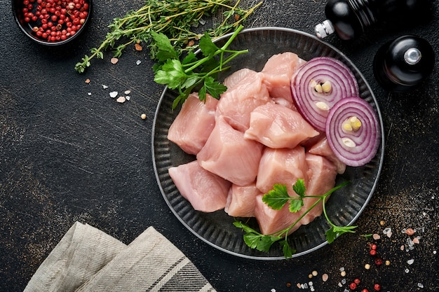 Rauwe stukjes vlees ingrediënten van kip op een houten bord, specerijen, kruiden en groenten
