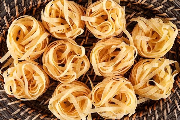 Rauwe tagliatelle pasta bal bovenaanzicht in een mandje