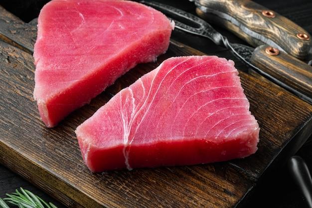 Rauwe tonijnfilet. zeevruchten met suiker groene erwt, sesam en ingrediënten set, op houten snijplank, op zwarte houten