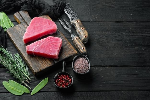 Rauwe tonijnsteak, verse rode tonijnfilet met ingrediënten, groene erwt, sesam en kruiden set, op houten snijplank, op zwarte houten tafel