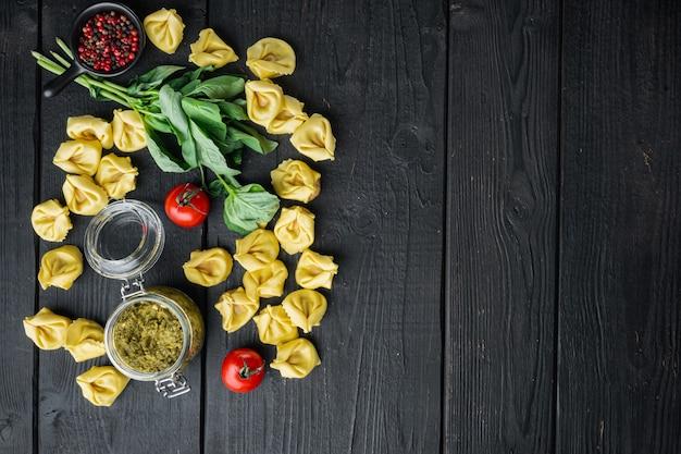 Rauwe tortellini met basilicum en pijnboompesto, op zwarte houten tafel, bovenaanzicht plat lag