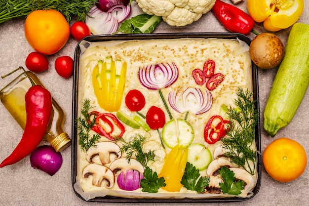 Rauwe tuin focaccia. vers deeg en groenten, olijfolie, groenen