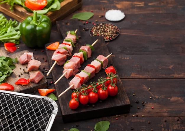 Rauwe varkenskebab met paprika op snijplank met verse groenten en wegwerp houtskoolgrill