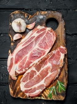 Rauwe varkenslapjes met aromatische en kruiden en specerijen. op een zwarte rustieke achtergrond.