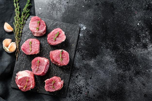 Rauwe varkensmedaillon steaks. varkensvleesfilet. zwarte achtergrond. bovenaanzicht. kopieer ruimte