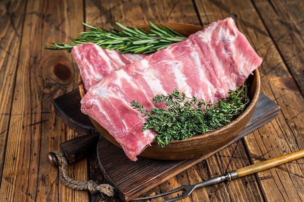 Rauwe varkensribbetjes in houten plaat met vleesvork. houten achtergrond. bovenaanzicht.