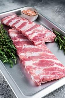 Rauwe varkensribbetjes in keukenblad met kruiden. witte achtergrond. bovenaanzicht.