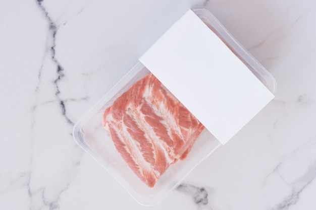 Rauwe varkensribbetjes in vacuümverpakking op marmeren achtergrond, logo mockup voor ontwerp.