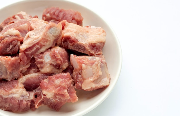 Rauwe varkensribbetjes in witte plaat op witte achtergrond.