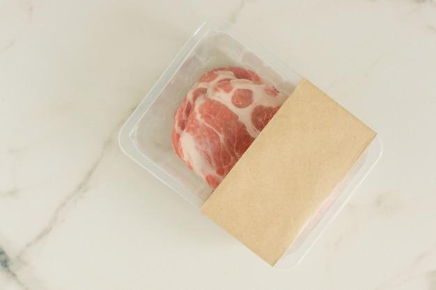 Rauwe varkenssteaks vacuüm verpakt op marmeren achtergrond, bovenaanzicht, mockup voor ontwerpers.