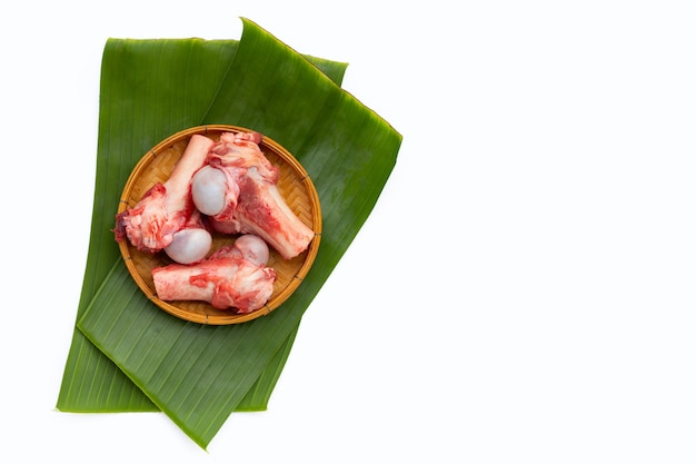 Rauwe varkensvlees botten op bananenbladeren op witte achtergrond.