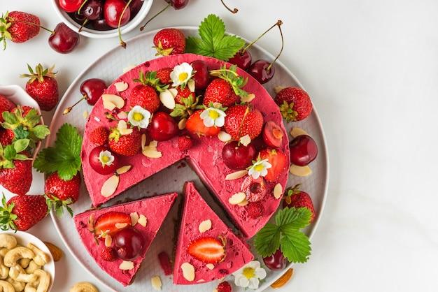 Rauwe veganistische cheesecake met bessen, cashewnoten, kersen, aardbeien, kokos, amandelen en dadels