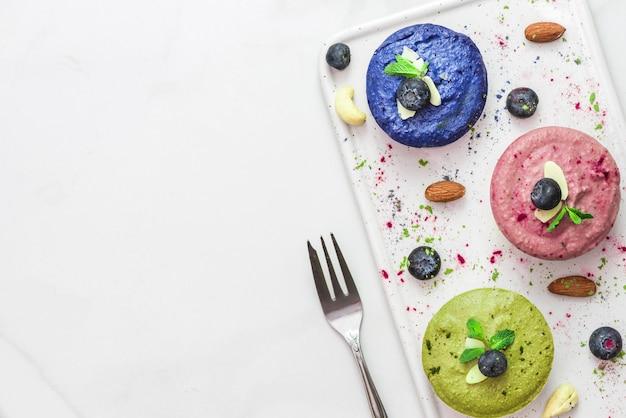 Rauwe veganistische kleurrijke taarten met matcha, acai, blauwe spirulina en butterfky erwtenthee, verse bessen, munt, noten. gezond veganistisch voedselconcept. bovenaanzicht. plat leggen