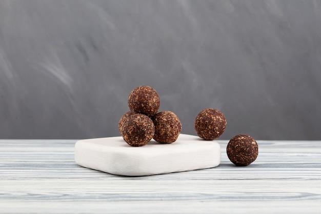 Rauwe veganistische snoepjes, energieballen met dadels, noten, gedroogd fruit en johannesbroodpoeder.
