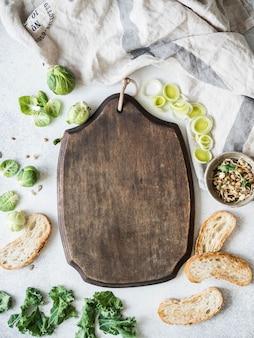Rauwe vegetarische ingrediënten voor het koken, ontkiemde zaden en sneetjes brood op tafel en blackboard in het midden voor receptenregistratie