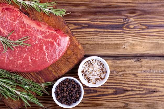Rauwe verse biefstuk geserveerd met rozemarijn en kruiden op rustieke houten bord