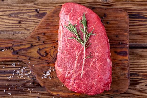 Rauwe verse biefstuk geserveerd met rozemarijn en verspreide kruiden op rustieke houten bord
