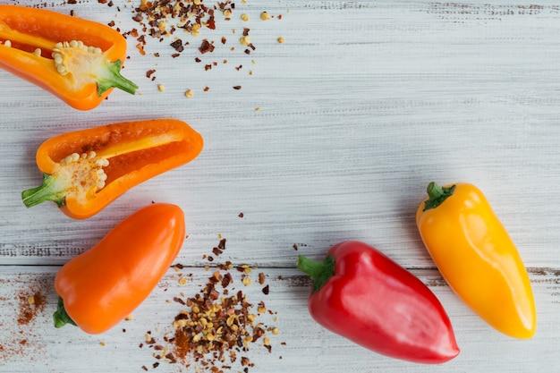 Rauwe verse biologische rode chili peper en diverse kruiden op witte houten tafel